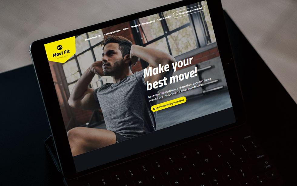 Aufgeklapptes, schwarzes Tablet steht auf einem Tisch und zeigt die Startseite der Website eines Fitnessstudios.