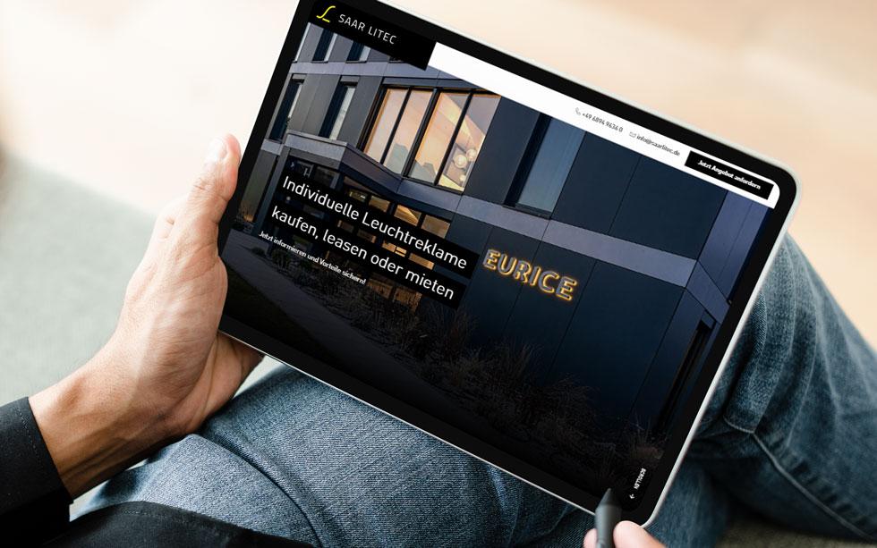 Webdesign Saarland - SL SAAR LITEC GmbH. Mann hält Tablet in der Hand und schaut sich eine Website für Leuchtwerbung an.