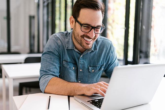 WordPress Wartung - Lächelnder Mann sitzt am Laptop